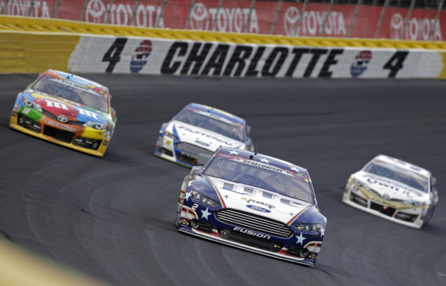 Driver Brad Keselowski (2) leads a pack of cars through Turn 4 during the NASCAR Sprint Cup series Coca-Cola 600 auto race at Charlotte Motor Speedway in Concord, N.C., Sunday, May 25, 2014. (AP Photo/Chuck Burton)