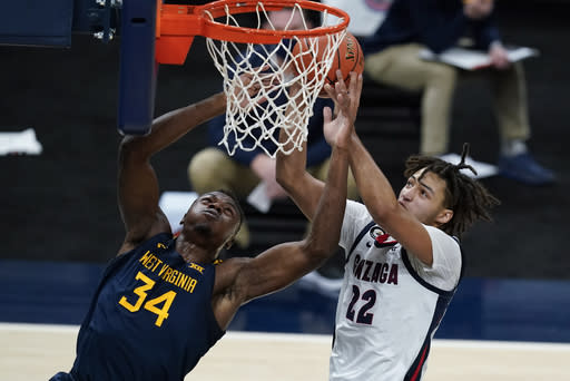 West Virginia's Oscar Tshiebwe (34) and Gonzaga's Anton Watson (22) vie for a rebound during the first half of an NCAA college basketball game Wednesday, Dec. 2, 2020, in Indianapolis. (AP Photo/Darron Cummings)