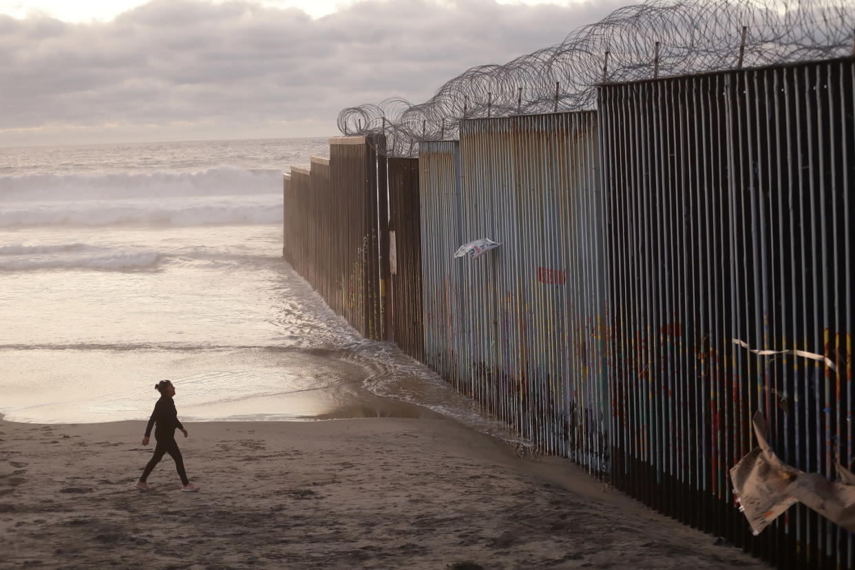 A woman walks on the beach next to the border wall topped with razor wire in Tijuana, Mexico on Jan. 9, 2019. (Photo: Gregory Bull/AP)