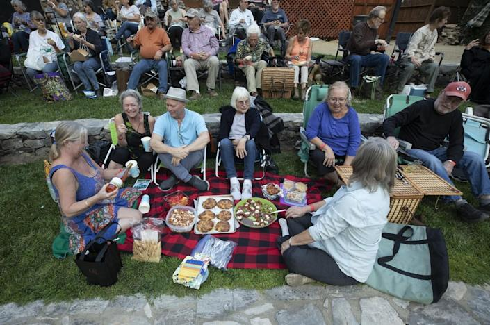 Playgoers sit around a picnic spread