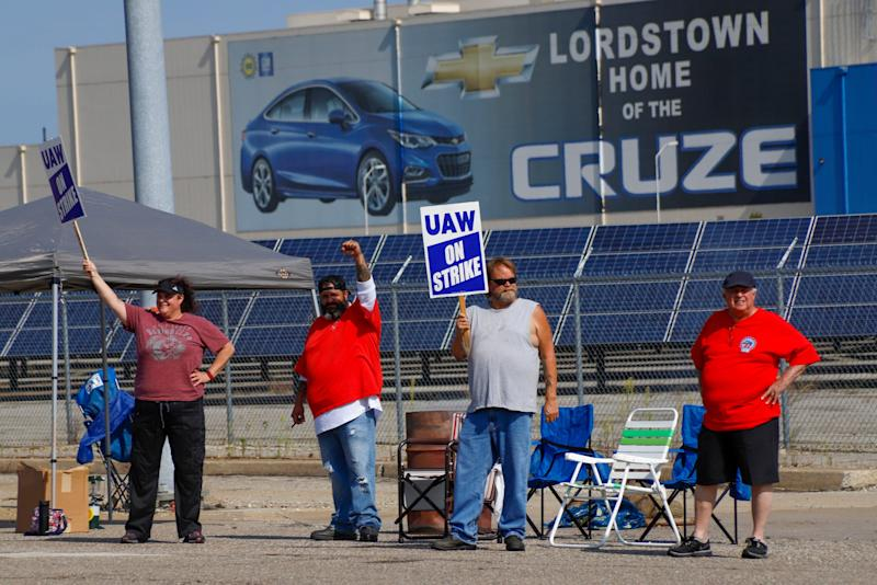 Picketers carry signs at one of the gates outside the closed General Motors automobile assembly plant,in Lordstown, Ohio on Sept. 16, 2019.