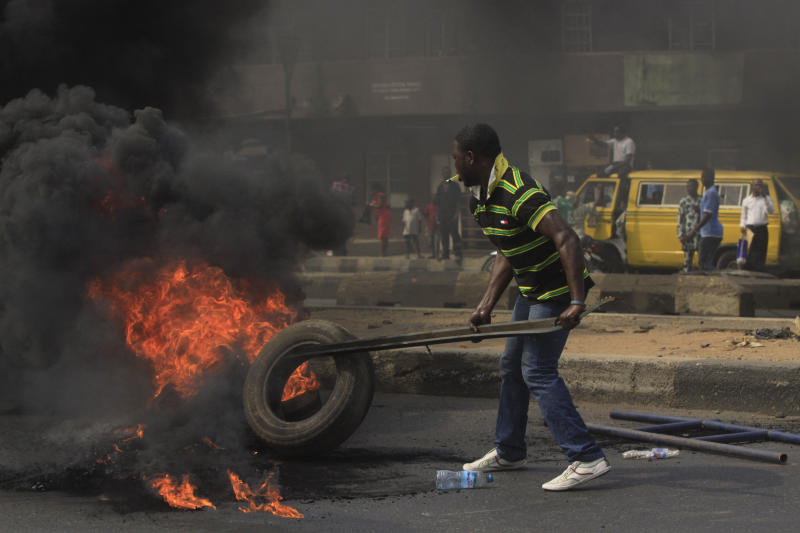 "FILE- An Unidentified man stocks the fire of a road block in the commercial capital of Lagos, Nigeria, during a fuel subsidy protest in this file photo dated Tuesday, Jan. 3, 2012, as angry mobs call on the government to keep a cherished consumer subsidy that had kept gas affordable for more than two decades. A 30-minute film documentary called ""Fuelling Poverty"" has been online for months, but it is revealed Sunday April 21, 2013, that Nigerian officials have refused its director Ishaya Bako permission to show it publicly in this oil-rich nation, as it focuses on the January 2012 protests and the alleged billions of dollars thought to have been swallowed up by greedy companies and the nation's elite.(AP Photo/Sunday Alamba, FILE)"