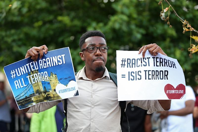 A man stands with anti-racism posters ahead of a vigil, close to the scene of a van attack in Finsbury Park, north London on June 19, 2017