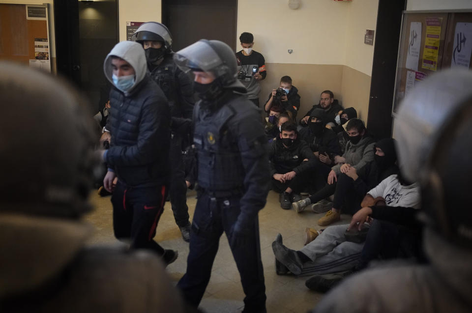 Rap singer Pablo Hasél, background, is surrounded by his supporters as police officers arrest one of the activists at the University of Lleida, Spain, Tuesday, Feb. 16, 2021. A rapper in Spain and dozens of his supporters have locked themselves inside a university building in the artist's latest attempt to avoid a prison sentence for insulting the monarchy and praising terrorism. (AP Photo/Joan Mateu)