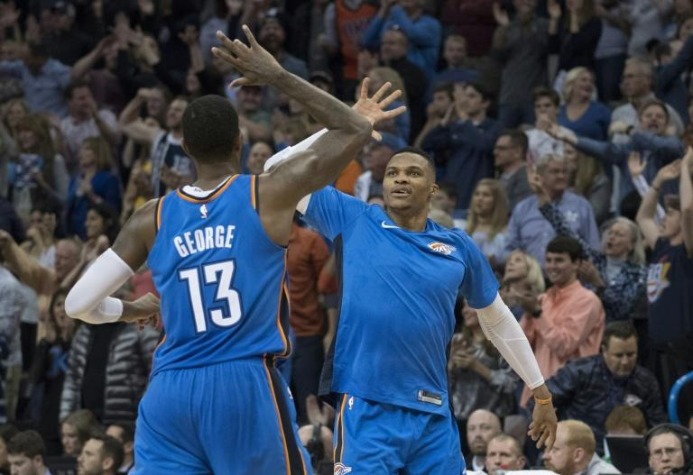 Paul George and Russell Westbrook of the Oklahoma City Thunder celebrate during the second half of their NBA game against the Golden State Warriors, at the Chesapeake Energy Arena in Oklahoma City, on November 22, 2017