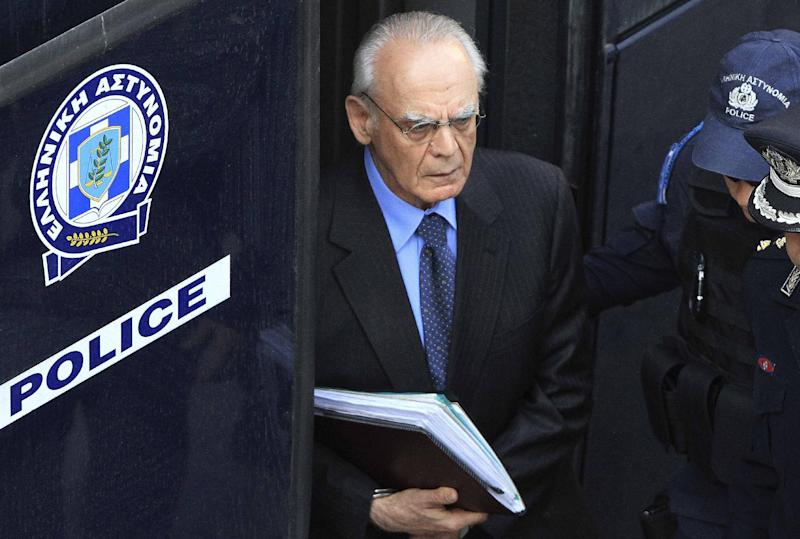 In this April 22, 2013 file photo, former Greek Defense Minister Akis Tsochadzopoulos, centre, arrives at court for the start of long anticipated corruption trial into allegations of kickbacks in defense contracts. An Athens court handed down a guilty verdict on Monday, Oct. 7, 2013 against the former defense minister on money laundering charges stemming from military purchases, in the most prominent corruption case to date in the financially-stricken country. (AP Photo/FOSPHOTOS/Panagiotis Tzamaros)