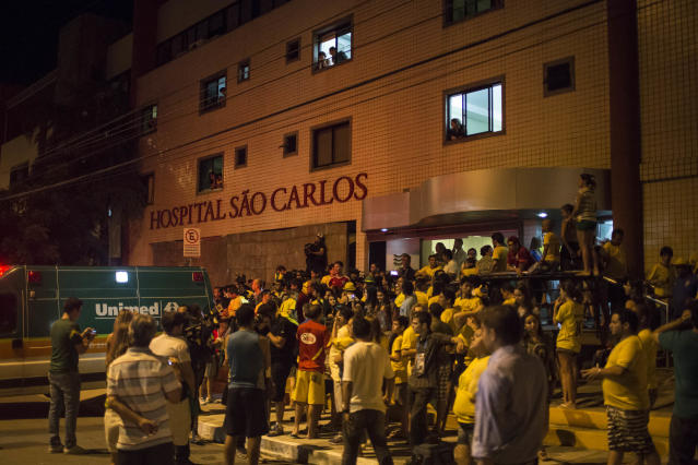 Soccer fans gather outside Sao Carlos Hospital where Brazil's soccer player Neymar was taken after being injured during the World Cup quarterfinal soccer match between Brazil and Colombia in Fortaleza, Brazil, Friday, July 4, 2014. Brazil's team doctor says Neymar will miss the rest of the World Cup after breaking a vertebrae during the team's quarterfinal win over Colombia. (AP Photo/Renata Brito)