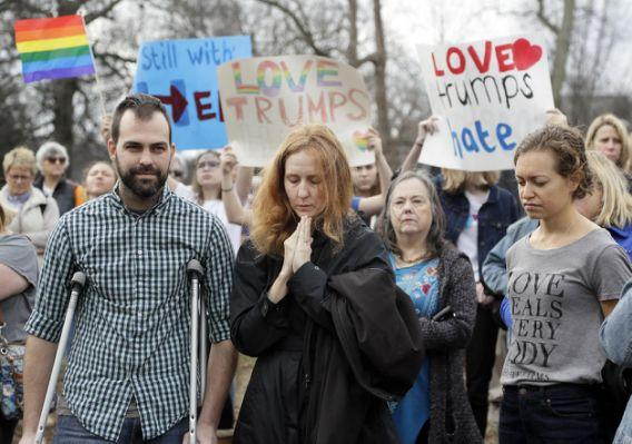 People take part in a protest Friday, Jan. 20, 2017, in Nashville, Tenn., organized to combat harsh rhetoric by Donald Trump. The protesters observed 15 minutes of silence during the time Trump took the Presidential oath of office in Washington. (AP Photo/Mark Humphrey)
