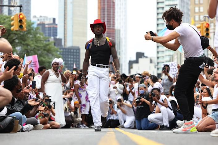People walk down a makeshift modeling runway as they take a break from marching during the Brooklyn Liberation's Protect Trans Youth event on June 13, 2021, in New York City.