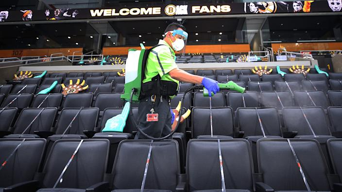 A worker wearking a face mask, face shield and backpack sprayer sanitizes empty seats at a stadium, some of which have foam hands placed in them..