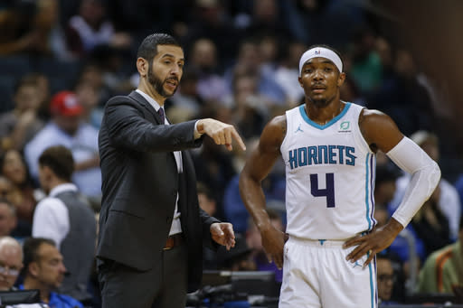 Charlotte Hornets head coach James Borrego, left, talks to Charlotte Hornets guard Devonte' Graham during a break in the action against the Sacramento Kings in the first half of an NBA basketball game in Charlotte, N.C., Tuesday, Dec. 17, 2019. (AP Photo/Nell Redmond)
