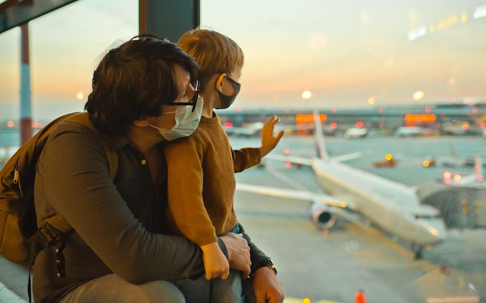 Father and son wearing masks at airport - Getty