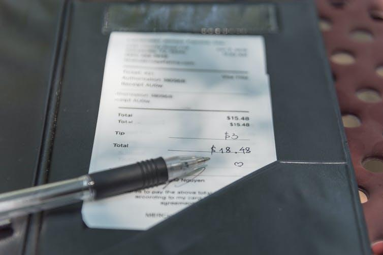 A signed credit card receipt on a restaurant table