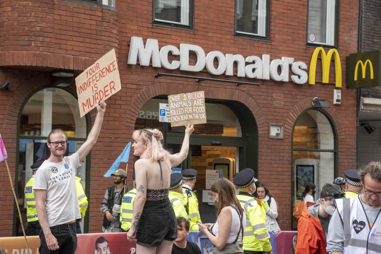 LONDON, UNITED KINGDOM - 2021/08/23: Animal Rebellion protesters hold placards outside a branch of McDonalds restaurant during the Extinction Rebellions day one of a two week demonstration in Central London. Extinction Rebellion held a protest against climate change, global warming, which plans to target the root cause of the climate and ecological crisis and to demand the government divest from fossil fuel companies ahead of COP26 the 2021 United Nations Climate Change Conference. (Photo by Dave Rushen/SOPA Images/LightRocket via Getty Images)