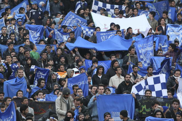 "FILE - In this Dec. 9, 2011 file photo, supporters of Iranian soccer team Esteghlal, hold flags of their favorite team, at the Azadi (Freedom) stadium, in Tehran, Iran. Sahar Khodayari, an Iranian female soccer fan died after setting herself on fire outside a court after learning she may have to serve a six-month sentence for trying to enter a soccer stadium where women are banned, a semi-official news agency reported Tuesday, Sept. 10, 2019. The 30-year-old was known as the ""Blue Girl"" on social media for the colors of her favorite Iranian soccer team, Esteghlal. (AP Photo/Vahid Salemi, File)"