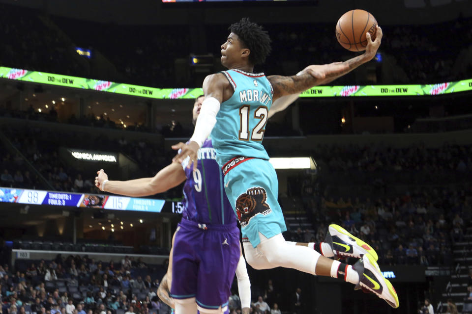 Memphis Grizzlies guard Ja Morant (12) goes up to shoots while defended by Charlotte Hornets center Willie Hernangomez (9) in the second half of an NBA basketball game Sunday, Dec. 29, 2019, in Memphis, Tenn. (AP Photo/Karen Pulfer Focht)