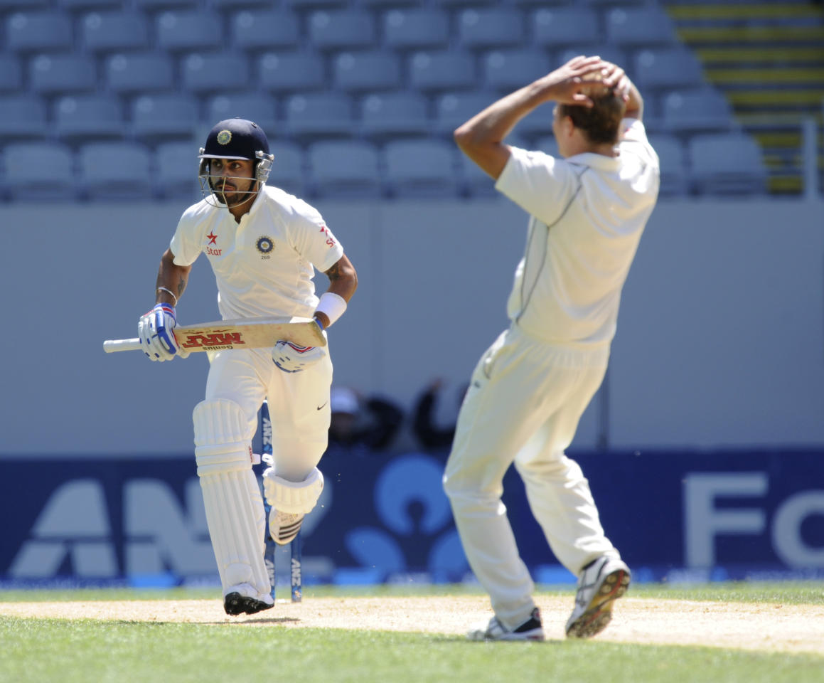India's Virat Kohli, left, runs past against despairing New Zealand's Neil Wagner on the fourth day of the first cricket test at Eden Park in Auckland, New Zealand, Sunday, Feb. 9, 2014. (AP Photo/SNPA, Ross Setford) NEW ZEALAND OUT