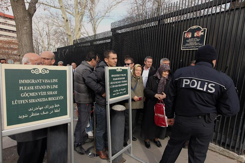 A Turkish police officer stands in front of people waiting for visas near the side entrance of the U. S. embassy, unseen, three days after a suicide bomber attack, in Ankara, Turkey, Monday, Feb. 4, 2013. The suicide bomber who struck the U.S. Embassy in Ankara spent five years in prison on terrorism charges but was released after being diagnosed with a hunger strike-related brain disorder, officials said Saturday. The bomber, identified as 40-year-old leftist militant Ecevit Sanli, killed himself and a Turkish security guard on Friday, in what U.S. officials said was a terrorist attack.(AP Photo/Burhan Ozbilici)