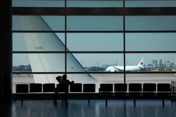 An airport worker watches planes on the runway at Toronto's Pearson International Airport on Friday. A 30-day federal ban on flights from India and Pakistan is now in effect amid rising COVID-19 cases in those countries. (Evan Mitsui/CBC - image credit)