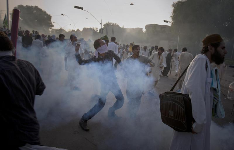 "A Pakistani protestor hurls back a tear gas canister fired by police during clashes that erupted as the demonstrators tried to approach the U.S. embassy in Islamabad, Pakistan, Friday, Sept. 21, 2012. Over a dozen people were killed as tens of thousands protested against the film around the country after the government encouraged peaceful protests and declared a national holiday — ""Love for the Prophet Day."" Demonstrations turned violent in several Pakistani cities. (AP Photo/Anjum Naveed)"