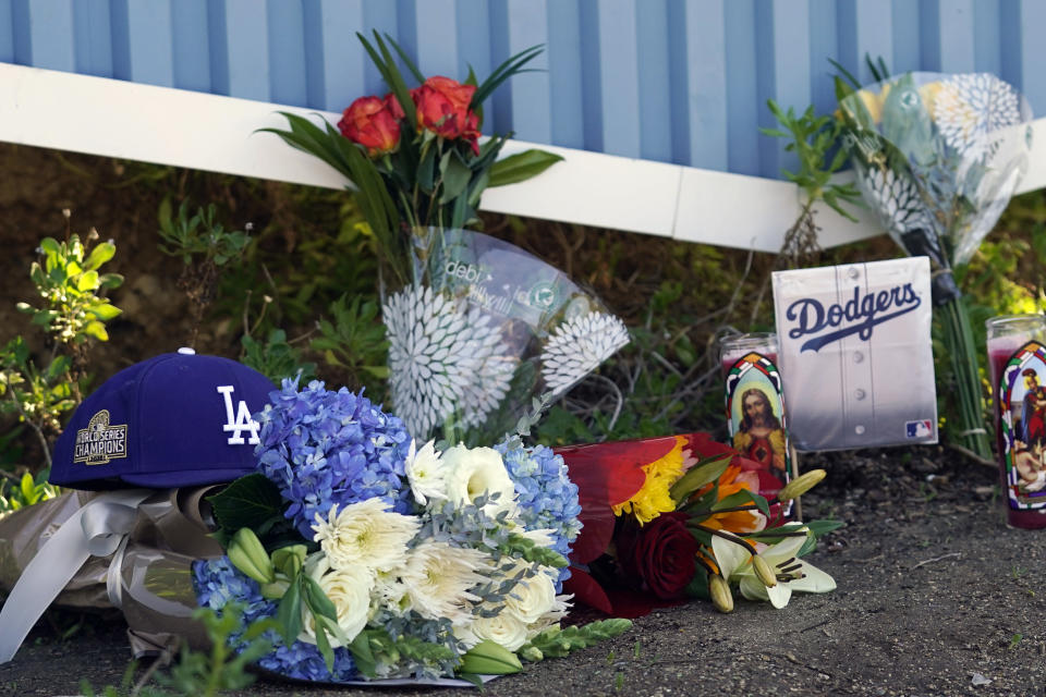 Memorabilia, flowers and candles are placed outside of Dodger Stadium Friday, Jan. 8, 2021, in Los Angeles. Tommy Lasorda, the fiery Hall of Fame manager who guided the Los Angeles Dodgers to two World Series titles and later became an ambassador for the sport he loved during his 71 years with the franchise, has died. He was 93. (AP Photo/Marcio Jose Sanchez)