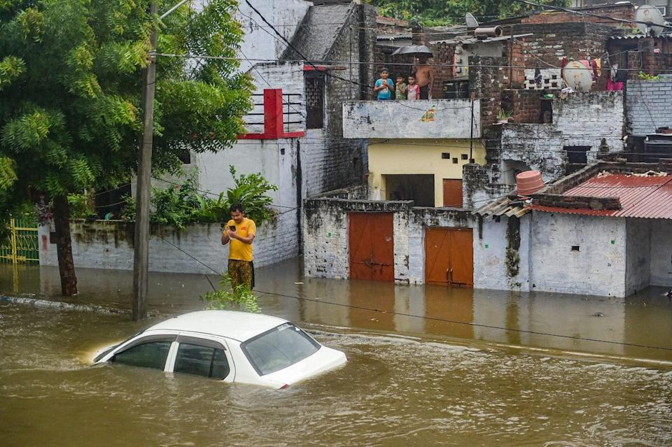 """<div class=""""paragraphs""""><p>Lucknow: A man stands near a partially submerged vehicle due to waterlogging following heavy rains on 16 September.</p></div>"""