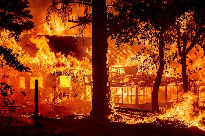 Flames from the Dixie Fire consume a home in the Indian Falls community of Plumas County, Calif., Saturday, July 24, 2021. The fire destroyed multiple residences as it tore through the area.