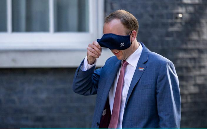 Matt Hancock removes his face mask as he arrives on Downing Street - Getty