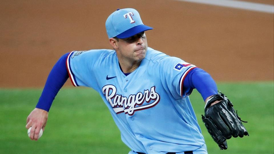 Corey Kluber delivers a pitch wearing powder blue Rangers uniform