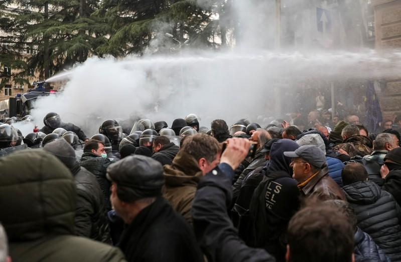 Riot police use a water cannon to disperse demonstrators during a protest against the government demanding an early parliamentary election in Tbilisi