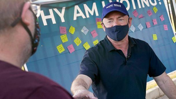 PHOTO: Mark Kelly, Democratic candidate for the Senate, greets voters at a polling station in Phoenix, Ariz., Nov. 3, 2020. (Matt York/AP)