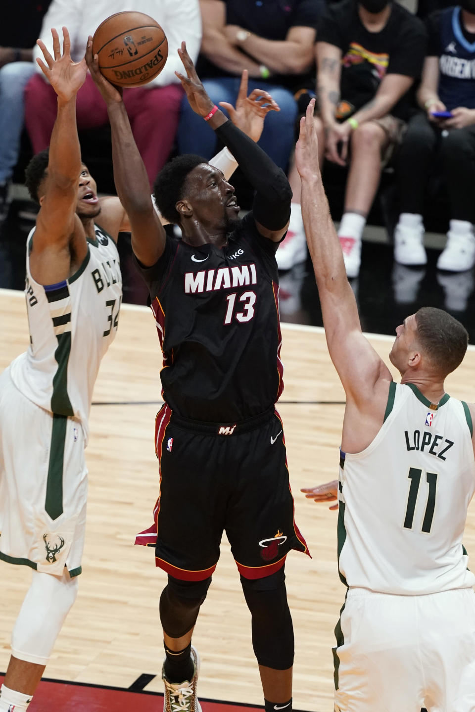 Miami Heat center Bam Adebayo (13) shoots as Milwaukee Bucks center Brook Lopez (11) and forward Giannis Antetokounmpo (34) defend during the first half of Game 3 of an NBA basketball first-round playoff series Thursday, May 27, 2021, in Miami. (AP Photo/Marta Lavandier)