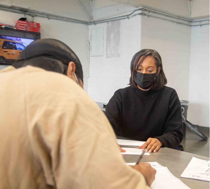 New York City Department of Correction Facility Programs Coordinator Nadely Tavarez works with a voter to complete voting forms at Rikers Island.