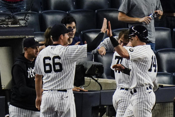 New York Yankees' Tyler Wade (14) celebrates with teammates after scoring on a sacrifice fly ball by Aaron Judge during the fifth inning of the second game of a baseball doubleheader Thursday, May 27, 2021, in New York. The Yankees won 5-3. (AP Photo/Frank Franklin II)