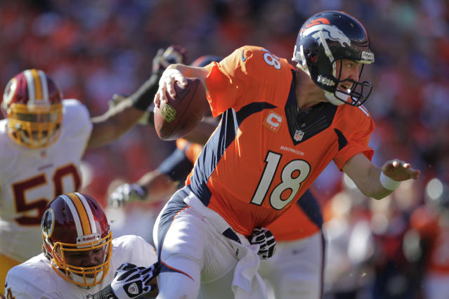 Denver Broncos quarterback Peyton Manning (18) pulls away from Washington Redskins linebacker Darryl Tapp (54) in the first quarter of an NFL football game, Sunday, Oct. 27, 2013, in Denver. (AP Photo/Joe Mahoney)