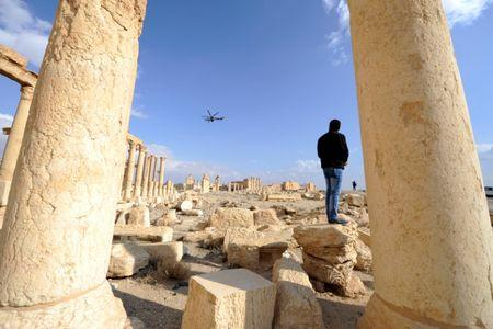 A man looks towards a Russian helicopter as it flies over ruins in the historic city of Palmyra, Syria March 4, 2017. REUTERS/Omar Sanadiki