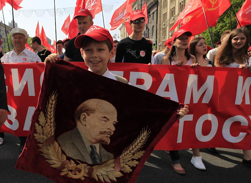 A child holds a portrait of Soviet founder Vladimir Lenin during a May Day rally in downtown Kiev, Ukraine, Wednesday, May 1, 2013. May Day, a holiday that was of great importance in the Soviet era is still marked with demonstrations in cities nationwide. (AP Photo/Sergei Chuzavkov)