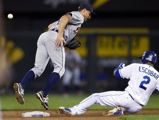 Kansas City Royals' Alcides Escobar (2) steals second base as the ball gets past Detroit Tigers second baseman Omar Infante (4) during the first inning of a baseball game at Kauffman Stadium in Kansas City, Mo., Monday, Oct. 1, 2012. Escobar advanced to third on the play. (AP Photo/Orlin Wagner)