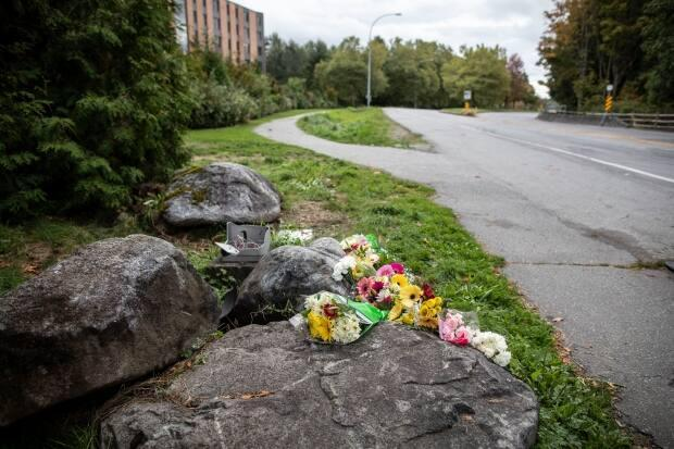 Flowers are pictured on Monday at a memorial for two UBC students who were struck and killed by a vehicle on the sidewalk of Northwest Marine Drive. (Ben Nelms/CBC - image credit)