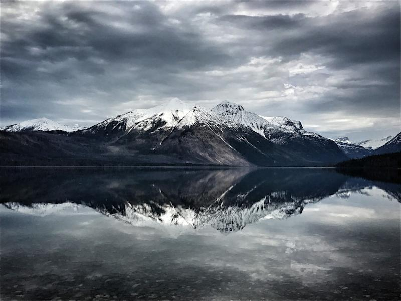 An ice-covered mountain is reflected in the clear water of Lake McDonald, the largest lake in Glacier National Park