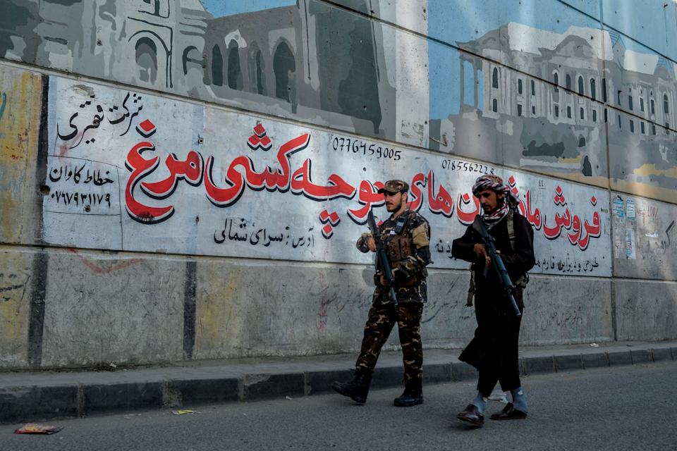Taliban fighters patrol along a road on the backdrop of a mural pained on the wall of a flyover in Kabul on September 26, 2021