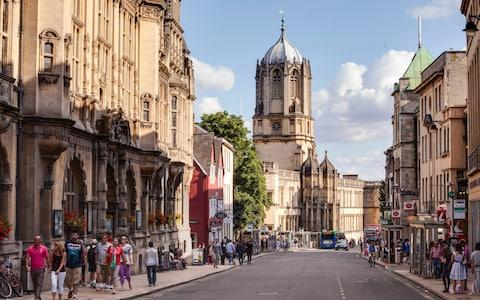 A busy street in Oxford. Christ Church cathedral can be seen rising above the rooftops. - Credit: Julian Elliott Photography/ Getty Images Contributor