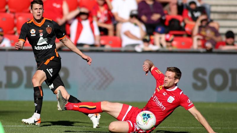 Ryan Kitto of United gets to the ball before Jake McGing of the Roar in their A-League clash