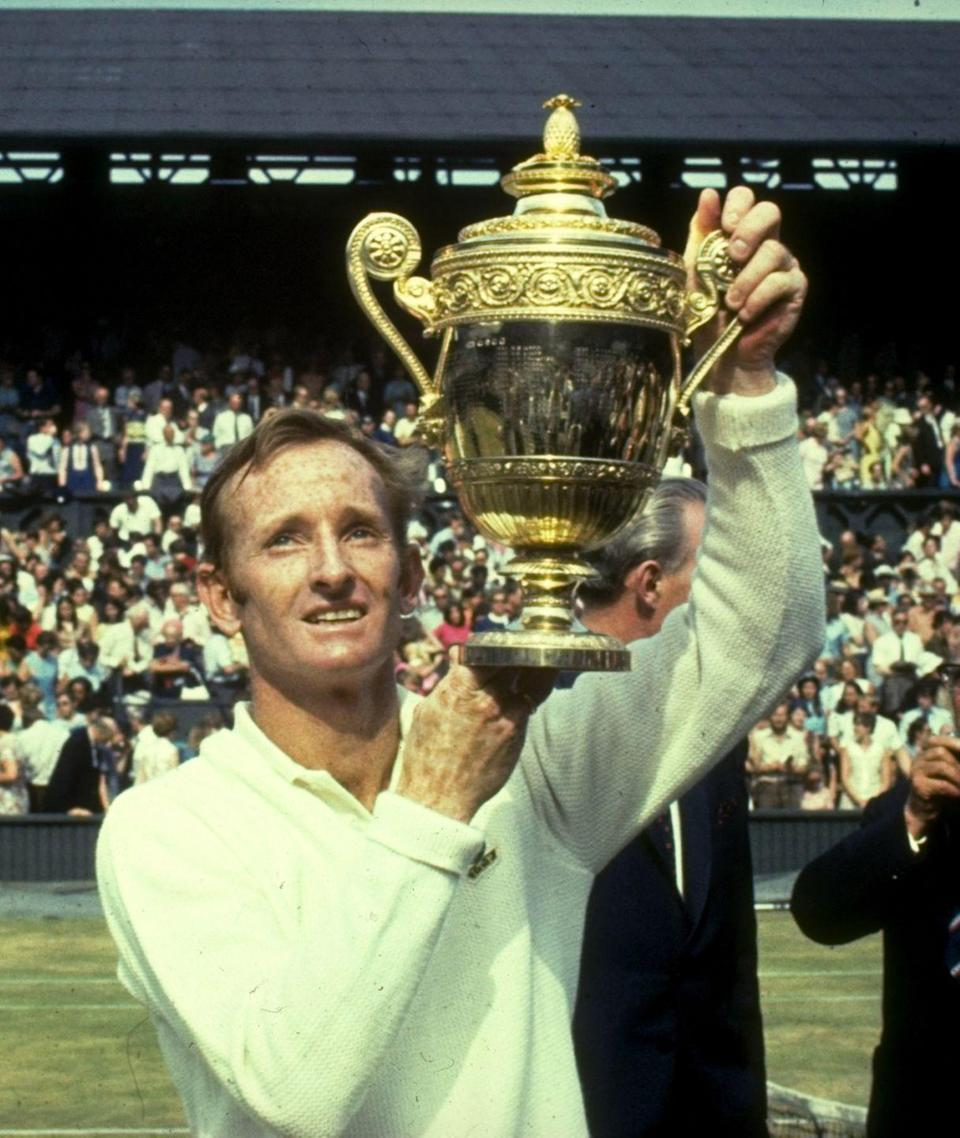 <p>Rod Laver of Australia holds the trophy aloft after his victory in the Men's Singles event in 1970.</p>