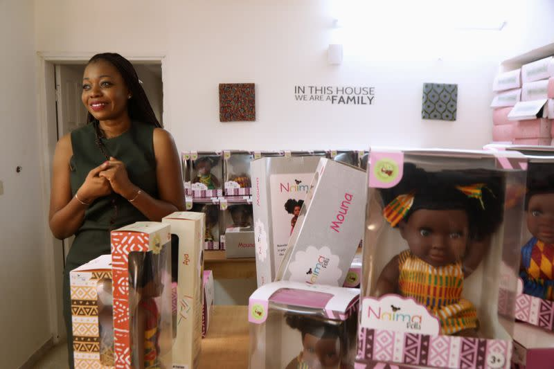 Sara Coulibaly, an Ivorian designer and creator of Naima Dolls brand of dark-skinned dolls, smiles as she stands at her workshop in Abidjan, Ivory Coast