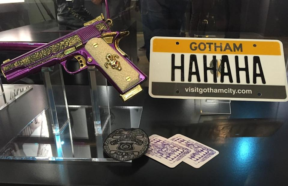 "<p>A purple handgun, ""Hahaha"" license plate, signature cards, and ""JTF Bravo"" security badge are part of the Joker's arsenal. JTF stands for ""Joint Task Force"" and the Squad's official name is Task Force X. The bottom of the badge refers to ""<a href=""https://www.biblegateway.com/passage/?search=Acts+26:16"" rel=""nofollow noopener"" target=""_blank"" data-ylk=""slk:Acts 26:18"" class=""link rapid-noclick-resp"">Acts 26:18</a>,"" a Bible verse about ""turning from darkness to light"" that serves as the team's mission statement. </p>"