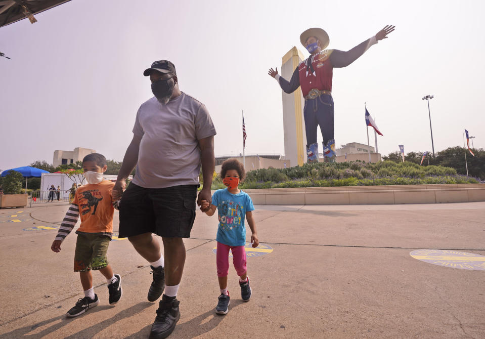 Wearing face masks to prevent the spread of COVD-19, Trey Lipscomb, center, holds the hands of his son, Trey, 6, and daughter Tia, 4, as they walk in front of Big Tex after getting their photo made during a visit to Fair Park in Dallas, Saturday, Sept. 19, 2020. Although the State Fair of Texas was canceled this year, fair organizers are holding drive-thru visits starting this weekend. (AP Photo/LM Otero)