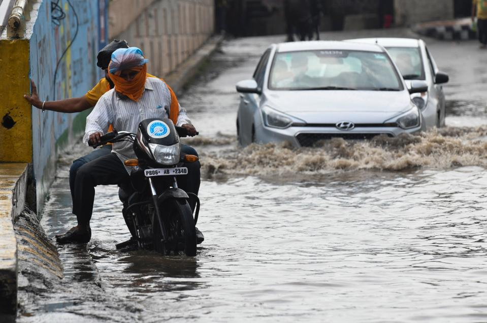 Commuter makes their way along a water-logged street following heavy rains in Amritsar on July 19, 2020. (Photo by NARINDER NANU / AFP) (Photo by NARINDER NANU/AFP via Getty Images)