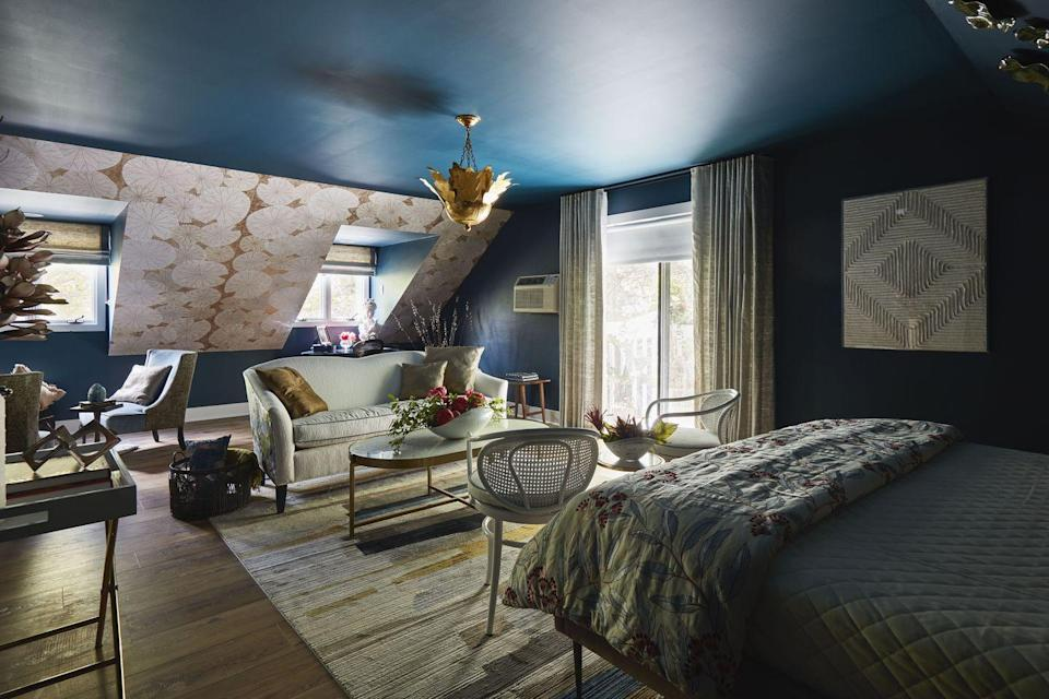 """<p>Prime views of the inn's courtyard and its koi pond aren't the only star of this suite, named for the late legend Cicely Tyson: Designers Denise Gordon, Tanya Lewis, and Marilyn Lavergne of the firm <a href=""""https://austingraydesigngroup.com/"""" rel=""""nofollow noopener"""" target=""""_blank"""" data-ylk=""""slk:Austin Gray Design Group"""" class=""""link rapid-noclick-resp"""">Austin Gray Design Group</a> (AGDG) brought the colors of the winter Berkshires landscape into this garret-like space through a cool and sophisticated palette. The walls are in River Blue by <a href=""""https://www.benjaminmoore.com/en-us"""" rel=""""nofollow noopener"""" target=""""_blank"""" data-ylk=""""slk:Benjamin Moore"""" class=""""link rapid-noclick-resp"""">Benjamin Moore</a>, while the sloped ceiling features a pop of pattern thanks to wallpaper from <a href=""""https://www.kravet.com/"""" rel=""""nofollow noopener"""" target=""""_blank"""" data-ylk=""""slk:Kravet"""" class=""""link rapid-noclick-resp"""">Kravet</a>. The designers carefully curated furniture that brought to mind both femininity and strength—just like Tyson. AGDG relished not only the design process, but also working with a cohort of accomplished BIPOC designers. """"The opportunity to learn and benefit from their years of diverse experience in the industry throughout the entire project made the experience for us priceless!"""" the group told us. </p>"""