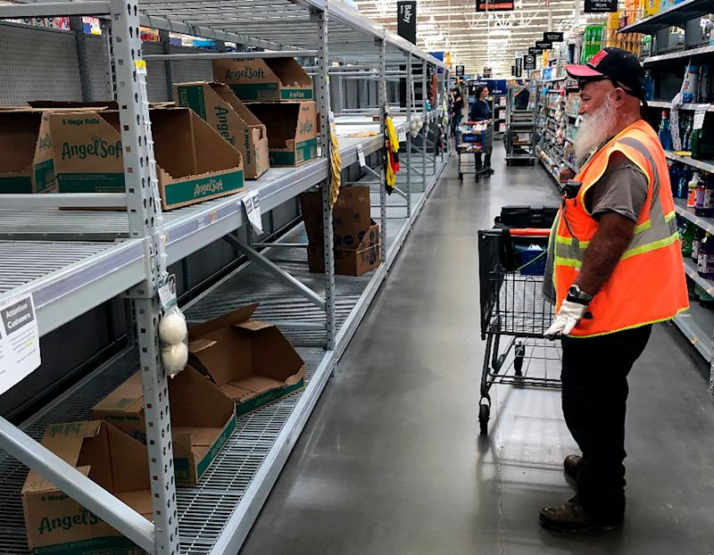 A shopper looks at a cleaned-out toilet paper aisle in a Phoenix Walmart, March 20. (ASSOCIATED PRESS)